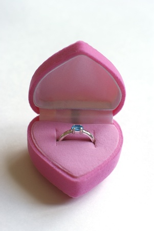 Pink heart-shaped box with engagement ring photo