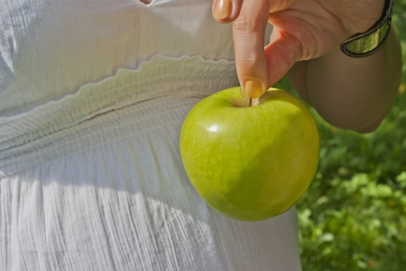 Pregnant woman is holding an apple photo