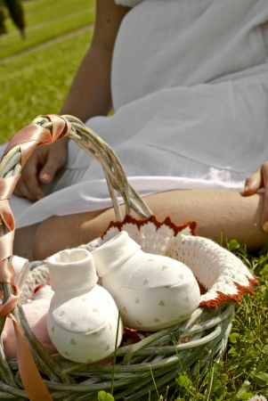 Pregnant woman is sitting on the grass with a gift basket Stock Photo
