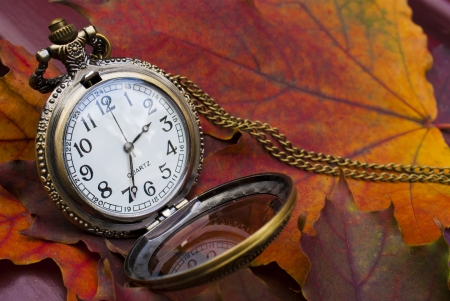 Abstract fall background with a pocket watch photo