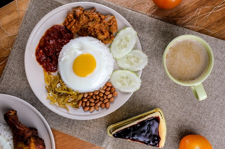 Nasi lemak is Malaysia favourite food which can be eaten with fried chicken or other foods. Stock Photo - 97357736