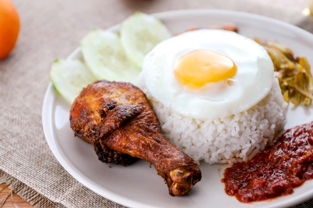 Nasi lemak is Malaysia favourite food which can be eaten with fried chicken or other foods. Stock Photo - 97357738