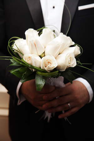beautiful wedding bouquet of white roses in hands of newlyweds Stock Photo
