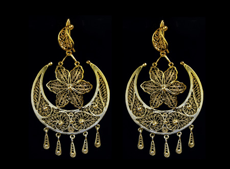 beautiful gold ornaments on a dark background. gold jewelry for women. necklace and earrings