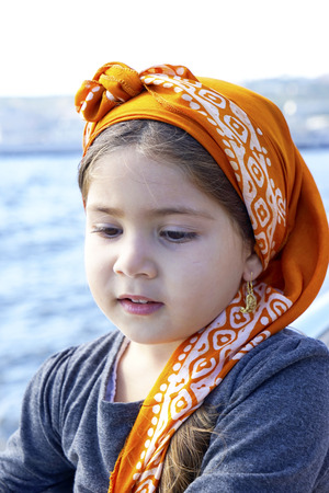 portrait of a pretty little cute girl in a headscarf on the sea, on a background of blue sky