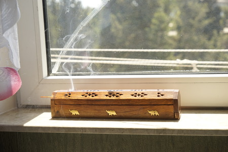 Agarbatti or Incense sticks emitting fragrant smoke Stock Photo