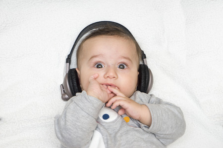baby with headphone lies on back, close up Stock Photo