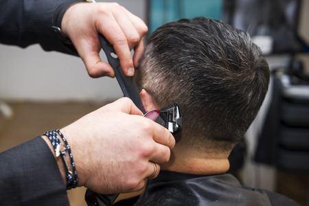 mens hairstyling and haircutting with hair clipper in a barber shop or hair salon,close up