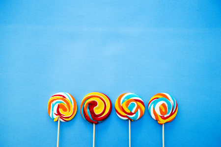 Colorful lollipop on a blue background. Red, white , orange and blue stripes on a candy. Minimal concept. Candy shop series.