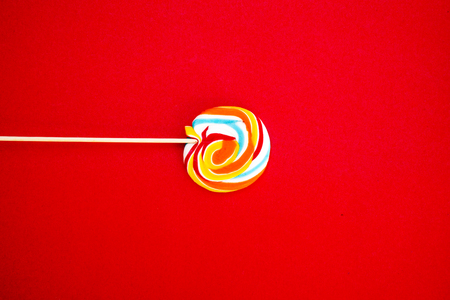 Colorful spiral lollipop candy on stick. On a red background.