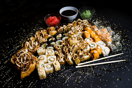 Set of traditional japanese food on a dark background. Sushi rolls, nigiri, raw salmon steak, rice, cream cheese, avocado, lime, pickled ginger. Asian food frame. Stock Photo