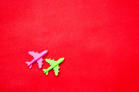 Flat lay of miniature toy airplane on pastel red background minimal trip and travel creative concepts. copy space