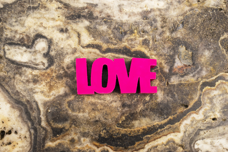 Red word love on a marble background with copy space.
