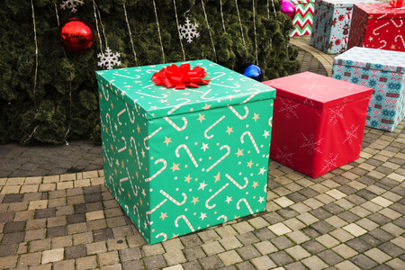 large beautiful multi-colored gift boxes lie near the Christmas tree. Banque d'images - 115813848