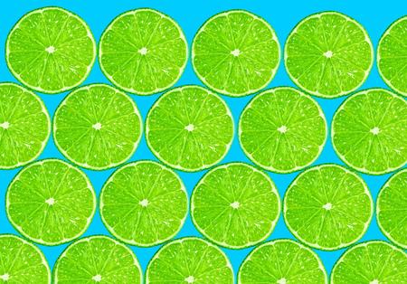 fresh slice of green lemon on blue background. texture.