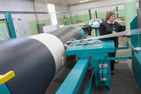 BAKU, AZERBAIJAN, 20 FEBRUARY 2018 : female labor working at the local looming factory with machinery equipment background to produce the colorful silk thread for the textile industry