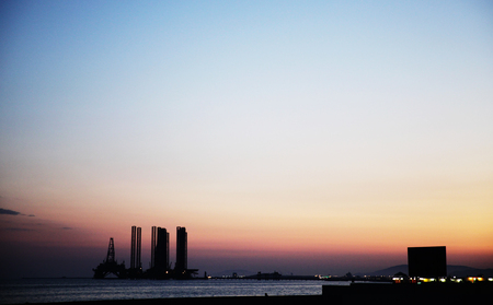 Silhouette of bridge connected offshore oil production platforms at oil field during sunset Banque d'images