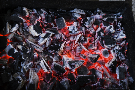 Smouldering black coals. Ashes in the barbecue.
