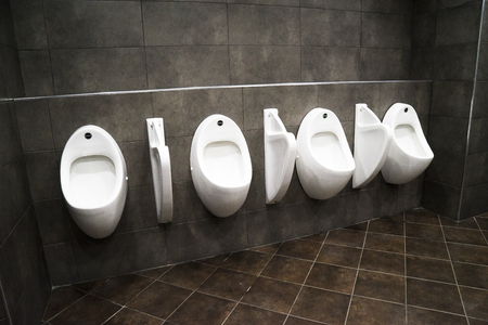 line of white porcelain urinals in public man toilets