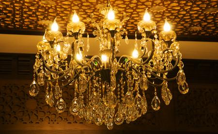 Lampadario da soffitto di forma classica in stile vintage realizzato in cristallo e vetro con lampade a forma di candela.