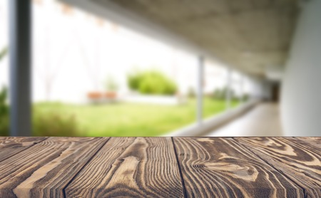 Wooden brown table top against the blurred corridor, passage and courtyard of the house .For product display montage or design is the key visual of the layout