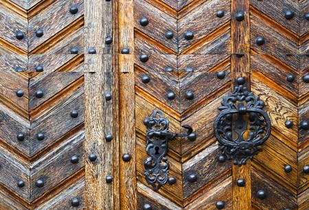 Puerta antigua marrón cerrada, portón con manijas de hierro. Foto de archivo