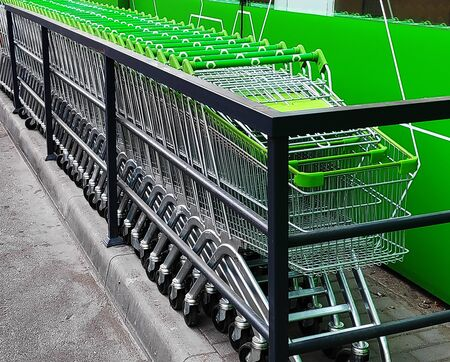 Green shopping carts together in a line up.