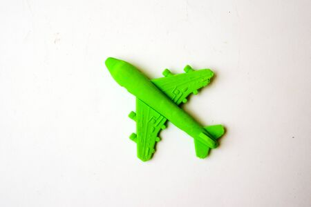 Children toy - green plastic plane with a red propeller, without a pilot, isolated on a white background