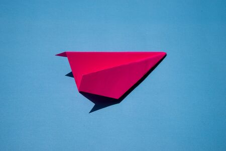 Pink Paper Plane or Paper Airplane Origami on Blue Background Top View with Place for Text, business competition concept