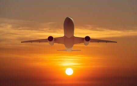 avion de passagers survoler la piste de décollage de l'aéroport au coucher du soleil, lever du soleil