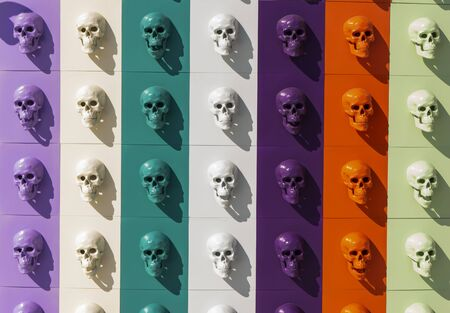 A collection of multi-colored skulls laid out in a line. Halloween concept.
