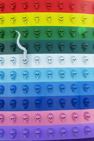 A collection of multi-colored skulls laid out in a line. Halloween concept