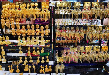 beautiful Indian, Oriental vintage women's gold earrings on shop window Standard-Bild - 132857417