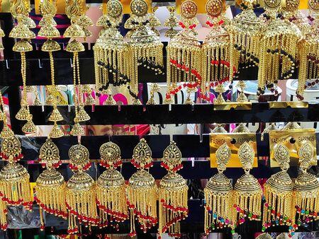 beautiful Indian, Oriental vintage women's gold earrings on shop window Standard-Bild - 132538103