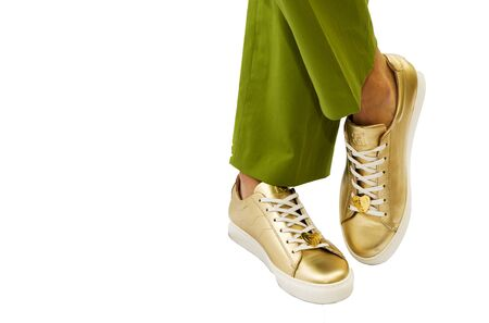 womens legs in green trousers and gold shiny sneakers on a white background. Imagens
