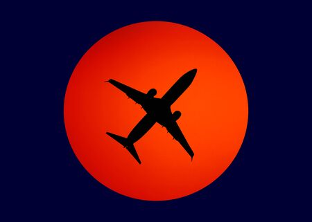 black silhouette of the plane against the orange sun in the blue sky Stock Photo