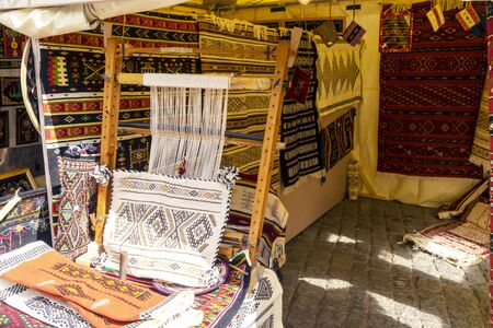 A traditional rug being woven on a carpet vertical loom, showing wool pile under tension, foundation, warp and weft.