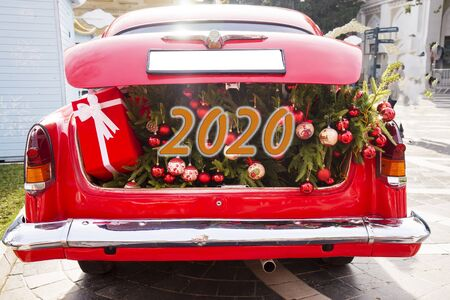 Un maletero rojo abierto lleno de bolsas de tela llenas de regalos y adornos navideños. Feliz Año Nuevo. 2020