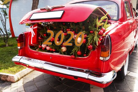 An opened red car trunk filled with cloth bags full of gifts and decorations for Christmas. Happy New Year. 2020 Stock Photo