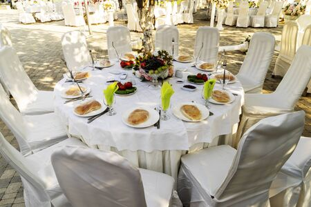 Elegant banquet tables prepared for a conference or a party and covered with a white tablecloth and decorated with flowers for guests Reklamní fotografie