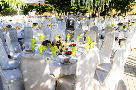Elegant banquet tables prepared for a conference or a party and covered with a white tablecloth and decorated with flowers for guests