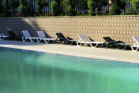beautiful luxurious swimming pool with crystal green waters in the garden.