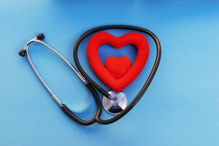 Health care check-up with red heart and Stethoscope on a blue background. Healing care concept and copy space. Above view of medical equipment for disease treatment on the blue backdrop