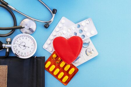 blood pressure monitor and red heart and pills on a blue background