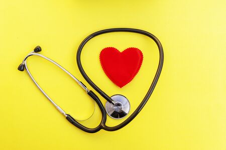 Top view stethoscope and red heart shape on yellow background. For check heart or health check up concept