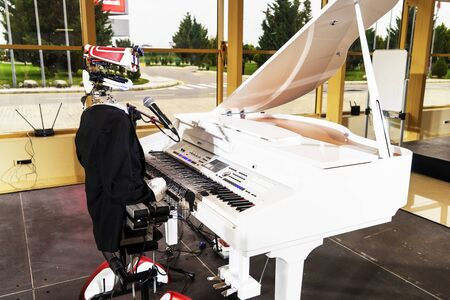 A robot in a black suit plays the white piano Stock fotó