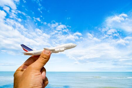 A mans hand holds a model airplane against a blue sky with white clouds