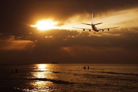The plane flies over the sea during sunset, sunrise