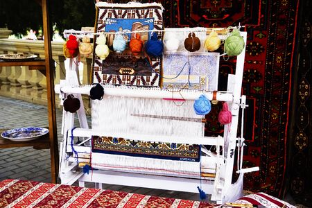 vintage wooden loom with half knit colored carpet on threads Stock fotó