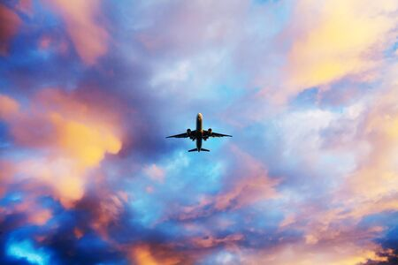 Airplane flying above dramatic clouds during sunset,sunrise Standard-Bild